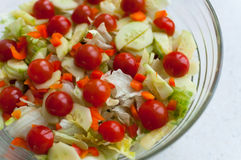 Vegetable salad. A glass bowl of green vegetable salad and cherry tomatoes Stock Photography
