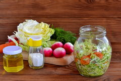 Vegetable salad in glass jar. Simple mixed vegetable salad. Salad with cabbage, carrots, radish, dill and olive oil. Vegetable salad. Fresh vegetables on cutting Stock Image