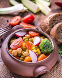 Vegetable salad in home crafted bowl with bread on wooden table. Stock Image