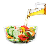 Vegetable salad with oil pouring from a bottle on white Royalty Free Stock Photography