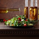 Green salad with olive oil pouring from a small bottle. Royalty Free Stock Photography