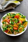 Vegetable salad with pieces of chicken meat. Healthy vegetable salad with pieces of chicken meat on dark stone background Royalty Free Stock Images