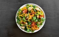 Vegetable salad with pieces of chicken meat. Tasty vegetable salad with pieces of chicken meat on dark stone background. Healthy food. Top view, flat lay Royalty Free Stock Photography