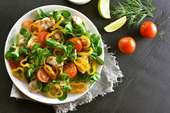 Vegetable salad with pieces of chicken meat. Tasty vegetable salad with pieces of chicken meat on dark stone background. Top view, flat lay Stock Photography