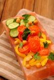 Vegetable salad on pink salt block on stripe napkin Stock Images