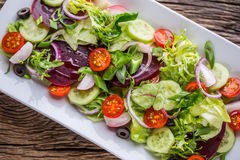Vegetable salad. Plate of salad with vegetables  on rustic oak table. Assortment of ingredients of vegetable salad Stock Photo