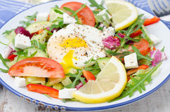 Vegetable salad with poached egg on a plate, closeup Royalty Free Stock Image