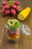 Vegetable salad with quinoa. Layered vegetable salad with quinoa, zucchini, carrots, garden radish and rocket with cashew nuts royalty free stock photography