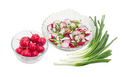 Vegetable salad of red radish with green onion. Vegetable salad of the fresh sliced red radish, green onion in transparent glass salad bowl and separately whole Stock Images