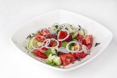 Vegetable salad from tomatoes, cucumbers, onions and greens. Healthy summer vegetable salad from tomatoes, cucumbers, onions and greens Stock Image
