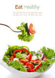 Vegetable salad in a white bow and on fork. Royalty Free Stock Photos