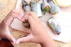 Vegetable salad wrapped into spring rolls with heart-shaped hands. Stock Photo