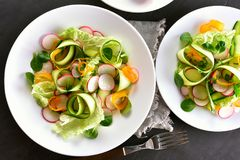 Vegetable salad from zucchini, radish, greens. Healthy vegetable salad from zucchini, radish, greens. Vegetarian vegan or natural organic food concept. Top view Royalty Free Stock Images