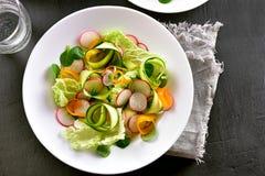 Vegetable salad from zucchini, radish, greens. Vegetarian vegan or healthy diet natural food concept. Tasty vegetable salad from zucchini, radish, greens. Top Stock Images