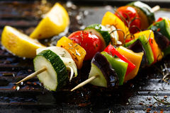 Vegetable skewers on the grill. Vegetarian grilled skewers with organic peppers, zucchini, tomatoes, eggplant and onions in herbal marinade Stock Photography