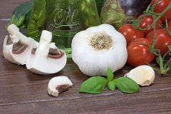 Vegetable and sliced mushrooms on the wooden table. Zucchini; eggplant, garlic, sliced mushrooms, basil leaves  and cherry tomatoes lying on a wooden table Royalty Free Stock Image