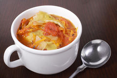 Vegetable soup. Hot mug of soup with tomato and vegetable filled ravioli stock photography