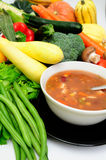 Vegetable Soup. In a bowl surrounded by fresh vegetables including squash, carrot, green beans, mushrooms, celery and bell peppers Royalty Free Stock Photography