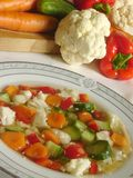 """Vegetable soup. Vegetable """"minestrone"""" soup with fresh veggies in the background Royalty Free Stock Photography"""