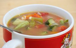 Vegetable Soup. Close up of Vegetable Soup in a White and Red Mug Royalty Free Stock Image