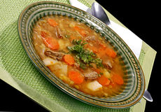 Vegetable soup. Soup made from fresh vegetables, served on green plate on table cloth underneet. Spoon on side Stock Photo