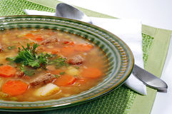 Vegetable soup. Soup made from fresh vegetables, served on green plate on table cloth underneet. Spoon on side Stock Photography
