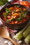 Vegetable soup with beans, carrots and celery close-up. vertical Stock Photos
