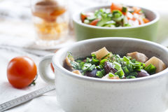 Vegetable soup with beans and chicken, fresh herbs in a clay pot Royalty Free Stock Photos