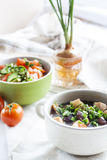 Vegetable soup with beans and chicken, fresh herbs in a clay pot Stock Photo