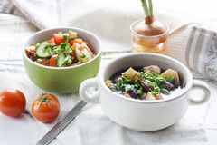Vegetable soup with beans and chicken, fresh herbs in a clay pot Stock Photos