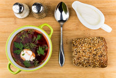 Vegetable soup, bread, salt, pepper and sour cream on table Royalty Free Stock Image