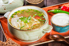 Vegetable soup, broth with noodles, herbs, parsley and vegetables in bowl with sour cream, spice, pepper, dried thyme and bread Stock Photos