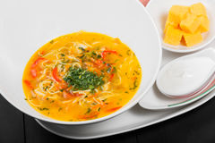 Vegetable soup, broth with noodles, herbs, parsley and vegetables in bowl on wooden black background, healthy food. Royalty Free Stock Photography