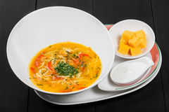 Vegetable soup, broth with noodles, herbs, parsley and vegetables in bowl on wooden black background, healthy food. Stock Photography