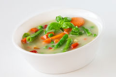 Vegetable soup with carrots and green beans and basil in white ceramic bowl on light background Stock Images