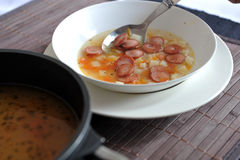 Vegetable soup with frankfurter sausages. Vegetable soup with added pieces of frankfurter sausages in a white deep plate next to a pot of soup on brown table Stock Photo