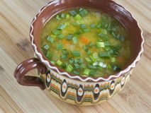 Vegetable soup with green onion in a clay bowl Stock Photos