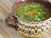 Vegetable soup with green onion in a clay bowl Stock Image