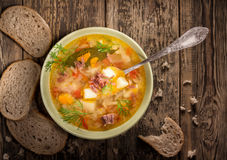Vegetable soup with meat. In a porcelain dish on a wooden background Royalty Free Stock Photo