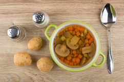 Vegetable soup with mushrooms, bread, salt, pepper and spoon. On wooden table. Top view Stock Images