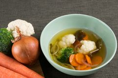 Vegetable soup with onion, carrot, cauliflower, broccoli and seaweed in green dish on brown tablecloth, and fresh vegetable next t. Vegetable soup with onion stock images