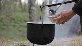 Vegetable soup outdoors in a cauldron stock video