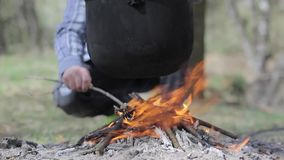 Cooking in a pot over campfire stock video footage