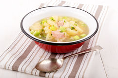 Vegetable soup with potatoes, celery and bacon cubes in an ename Stock Photography