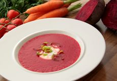 Vegetable soup with red beet, carrots and tomatoes. Red beet soup with carrots and tomatoes. Served with cream and leek Stock Images