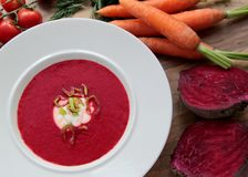 Vegetable soup with red beet, carrots and tomatoes. Red beet soup with carrots and tomatoes. Served with cream and leek Royalty Free Stock Photo