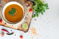 Vegetable soup with red lentils and tomatoes on the white table. stock photo
