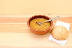 Vegetable soup served with seasoning and bread roll Royalty Free Stock Photo