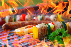 Barbecue with flames and vegetable spit Stock Images