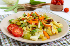 Vegetable stew - a mixture of baked cabbage, green beans, onions, carrots, cherry tomatoes, sweet pepper on a plate Royalty Free Stock Photos